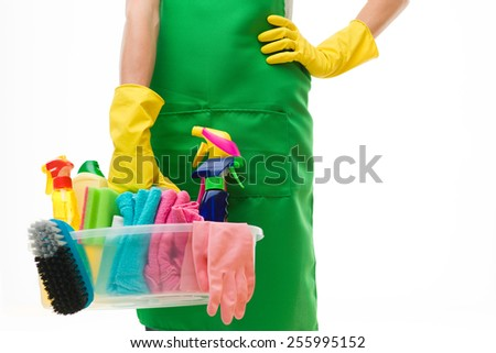close-up of caucasian cleaning lady holding basin with cleaning supplies, against white background - stock photo