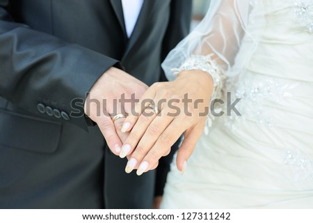 close-up of caucasian couple's hands with wedding rings - stock photo