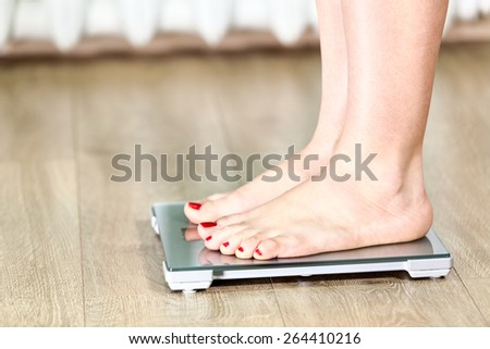 Close up of Caucasian female legs standing on the floor scales - stock photo
