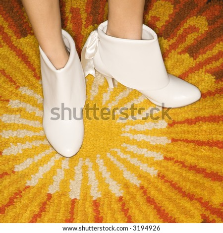 Close-up of Caucasian mid-adult female feet in white vintage boots against sunburst rug. - stock photo