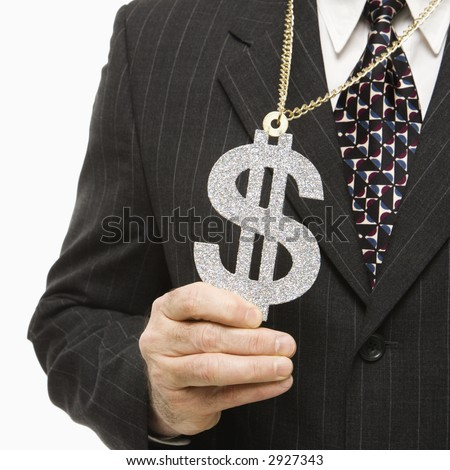 Close-up of Caucasian middle-aged businessman wearing chain necklace with oversized dollar sign.