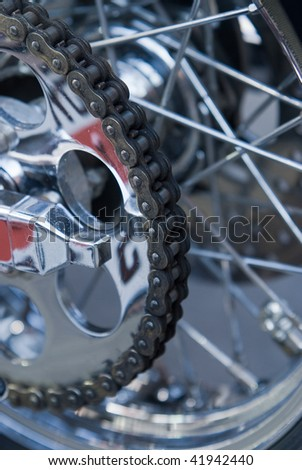 Close-up of chain on heavy motorbike with many chrome parts. Very shallow depth of field with top half of the chain in focus.