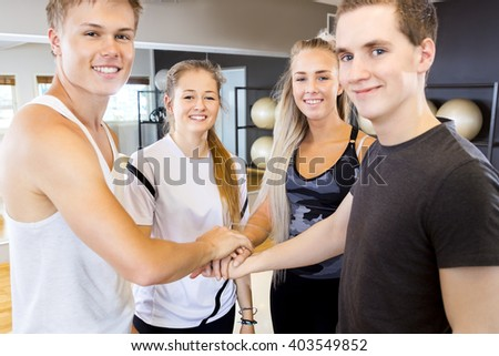 Close-up of cheerful fitness workout team holding hands - stock photo