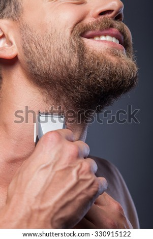 Close up of cheerful guy shaving his beard. He is holding electric razor. The man is standing and smiling - stock photo