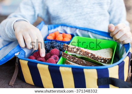 close-up of cheerful schoolboy eating healthy lunch outdoor