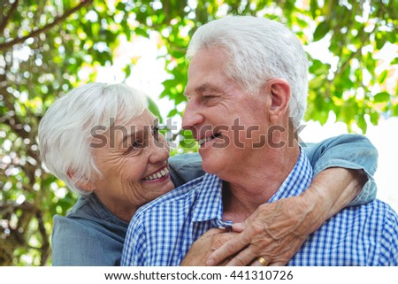 Close-up of cheerful senior couple hugging while standing outdoors - stock photo