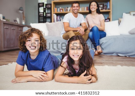 Close-up of cheerful son and daughter lying on carpet while parents sitting on sofa at home - stock photo