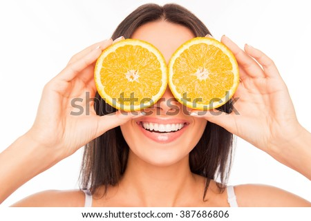 Close up of cheerful woman holding two halves of orange near eyes