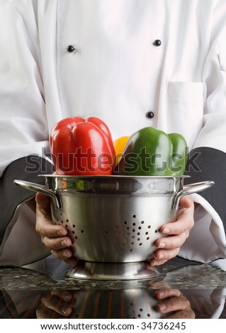 Close Up of Chefs Hands Holding Strainer with Vegetables - stock photo
