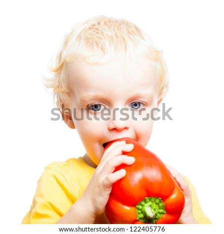 Close up of child boy eating red sweet pepper, isolated on white background. - stock photo