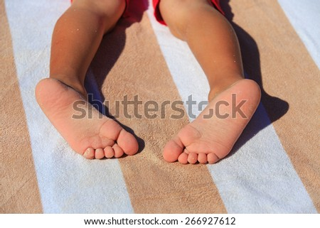close up of child feet  covered with sand on beach towel - stock photo
