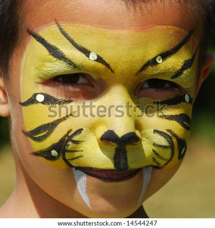 close-up of child painted in the face as a tiger