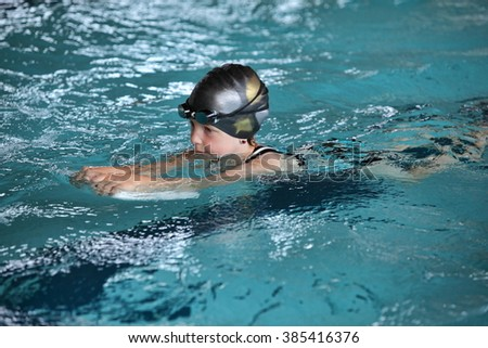 Close up of child practicing flutter kick with kick board in  indoor swimming pool
