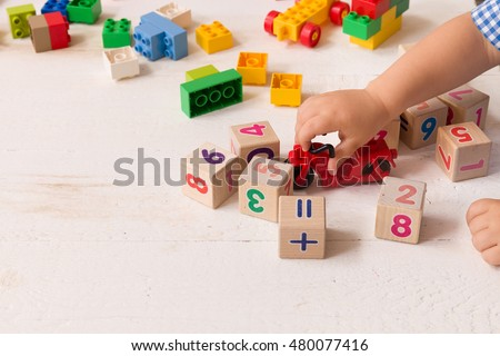 Close up of child's hands playing with colorful plastic bricks and red motorcycle at the table. Toddler having fun and building out of bright constructor bricks. Early learning.   Developing toys