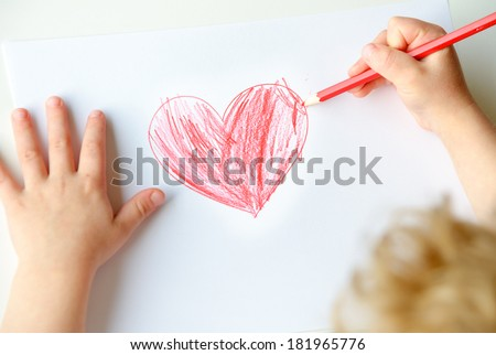 Close-up of childs hands drawing a red heart - stock photo