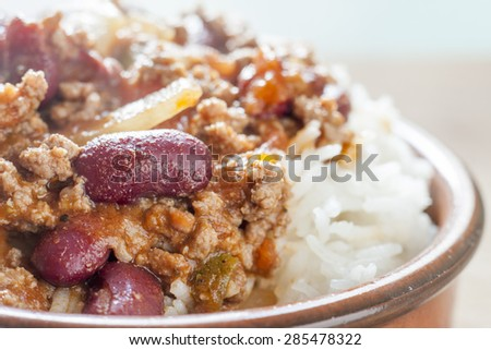 Close-up of chilli con carne and rice in a terracotta dish - stock photo