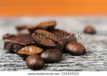 close up of chocolate and coffee beans on wooden background - stock photo