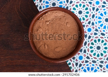 close up of chocolate powder in a bowl on blue background - studio shot  from above - stock photo
