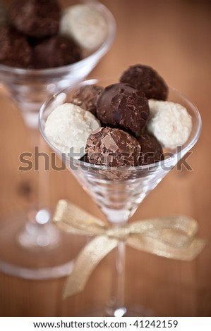 Close up of chocolate truffles in elegant glasses, one glass with gold ribbon - stock photo