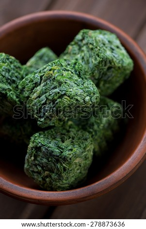 Close-up of chopped and compressed fresh spinach, studio shot - stock photo