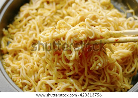 close up of chopsticks stirring cooking instant noodles in frying pan  - stock photo