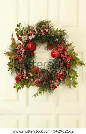 Close-up of Christmas fruit themed wreath decoration with red apples and berries on a white wooden door  - stock photo