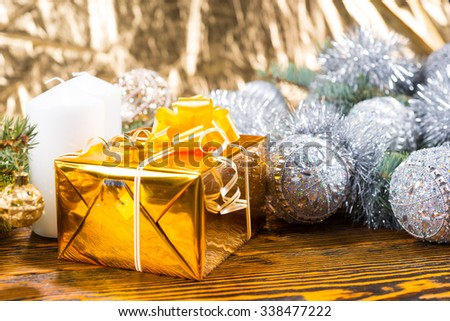 Close Up of Christmas Gift Wrapped in Gold on Rustic Wooden Table with Candle and Evergreen Branches Decorated in Silver Garland and Balls - stock photo