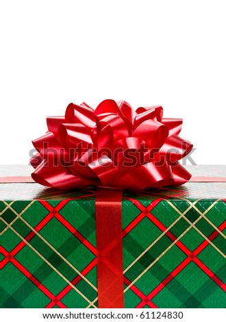 Close up of Christmas gift wrapped in green and red plaid paper with red bow on top. - stock photo