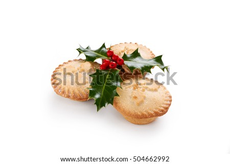 Close up of Christmas Mince Pies and holly sprig isolated on a white background