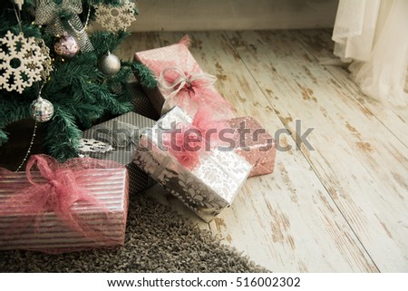 Close-up of Christmas presents under the fir on the floor