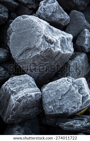 Close up of chunks black coal on which the is visible rime. Morning snow on the rocks of coal - stock photo
