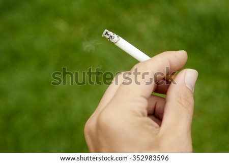 Close-up of cigarette is in the hand of man - stock photo