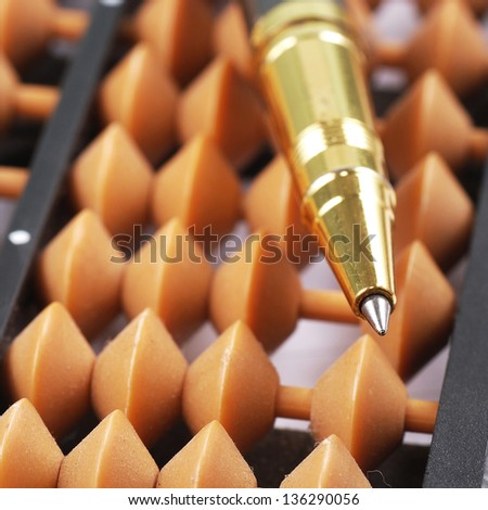 Close-up of classic abacus with gold pen - stock photo