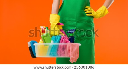 close-up of cleaning lady holding supplies, on orange background - stock photo