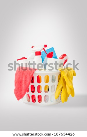 Close up of cleaning products and supplies in a basket. Cleaners, microfiber cloths, gloves in a basket isolated on white background. Cleaning kit. - stock photo