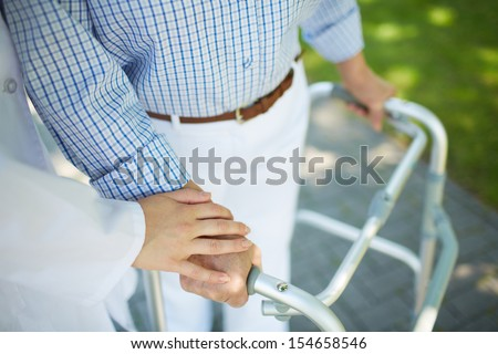 Close-up of clinician hand on that of disabled woman - stock photo