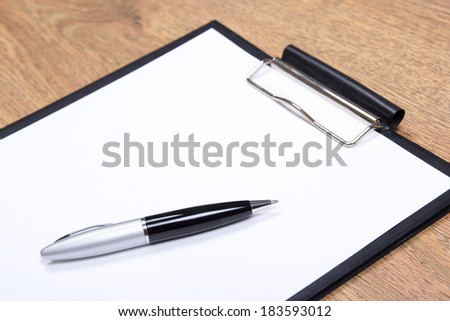 close up of clipboard with blank paper and pen on wooden table