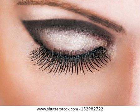 Close-up of closed beautiful eye with long sexy false lashes - stock photo