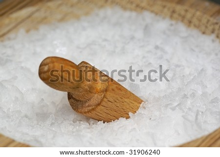 Close-up of coarse salt with wooden spoon - stock photo