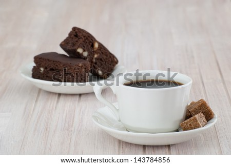 Close-up of coffee cup and brownies on a  white table