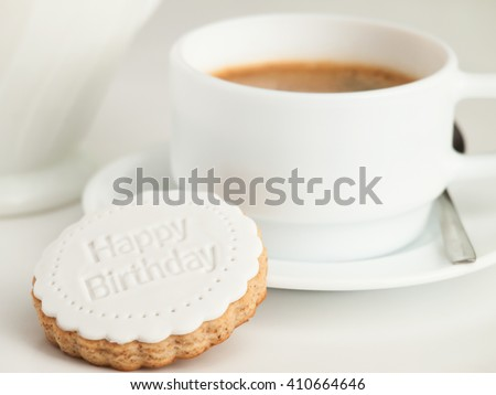 Close up of coffee cup and fondant covered cookie. Happy birthday decoration on top. - stock photo