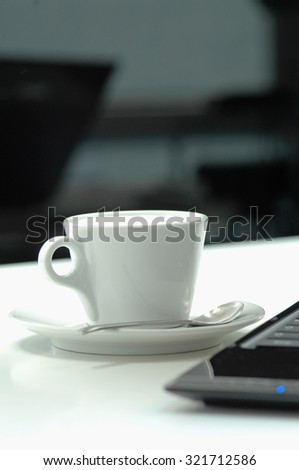 Close up of coffee cup with laptop on table