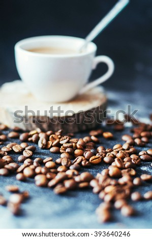 Close-up of coffee cup with roasted coffee beans on black background. Close-up of a cup of coffee. Cup of coffe. Delicious coffe cup on black tablecloth. Hot coffee in a cup on a round wooden stand. - stock photo