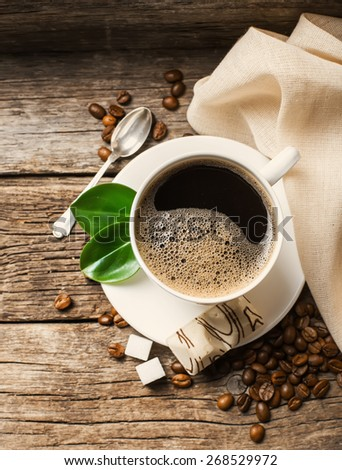 Close-up of coffee cup with roasted coffee beans on wooden background. - stock photo