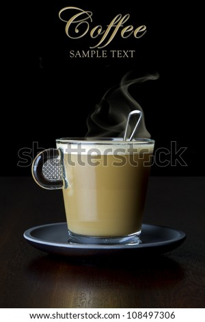 Close-up of coffee with milk in a glass cup on a saucer, resting on a wooden table, Sample text can be removed easily. - stock photo