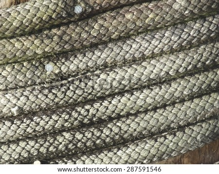 Close up of coiled rope on wharf - stock photo