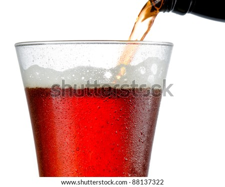 Close up of cold beer pouring into a frosted pilsner style glass almost full with no head formed - stock photo