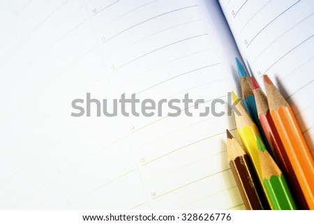Close-up of color pencils and agenda - stock photo