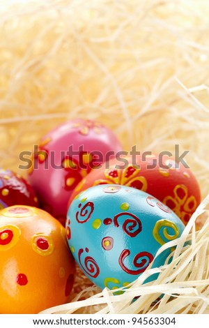 Close-up of colored and decorated Easter eggs in straw - stock photo