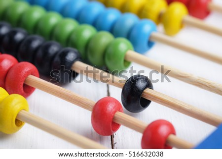 Close up of colorful abacus, traditional abacus in front of white background, selective focus.